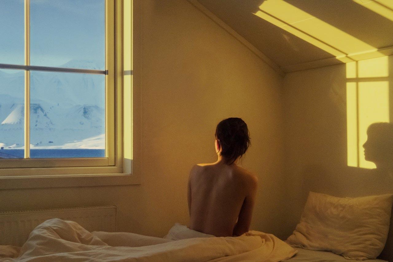 Femme regarde par la fenêtre en Italie